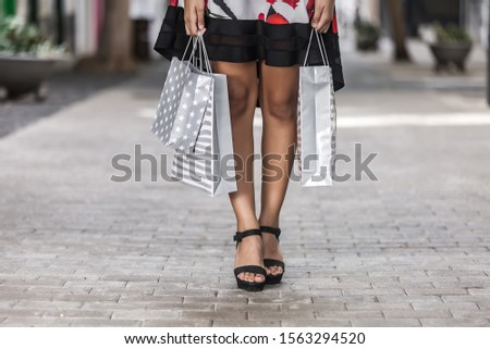 Crop legs in glamours shoes of woman in dress carrying shopping bags on sidewalk #1563294520