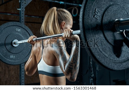 Female bodybuilder doing back squats in gym Beautiful young brunette getting ready to do barbell squats wearing a black and white top Muscular young fitness woman lifting a weight crossfit in the gym #1563301468