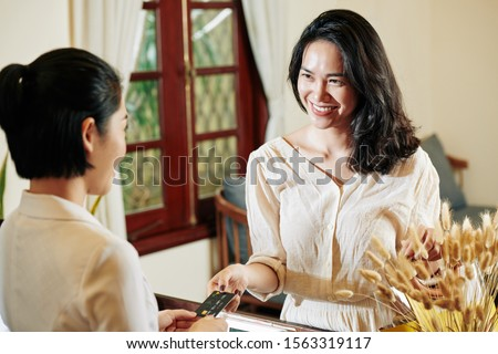 Beautiful smiling young Asian woman giving credit card to receptionist to pay for treatment in spa salon