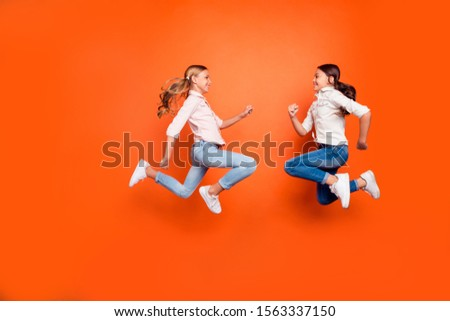 Full size profile side photo of positive funny two kids relax rest jump run play game  wear white shirt denim jeans sneakers isolated orange color background #1563337150