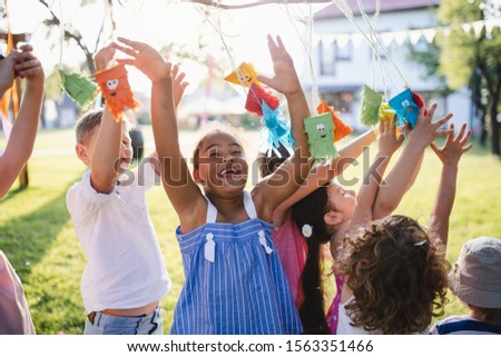 Small children standing outdoors in garden in summer, playing. #1563351466
