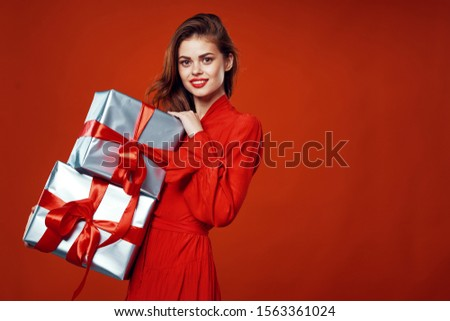 Beautiful woman in a red dress holds big gift boxes in her hand #1563361024