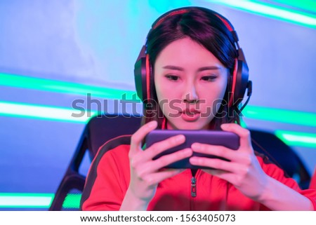 Close Up of young asian teenage cyber sport gamer play mobile game by smartphone on eSport tournament #1563405073
