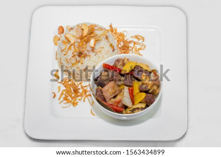 A plate of home chef Beef Kata Masala, plane flavourful nutty pulao and little poteto fried. Top view. on white background. #1563434899