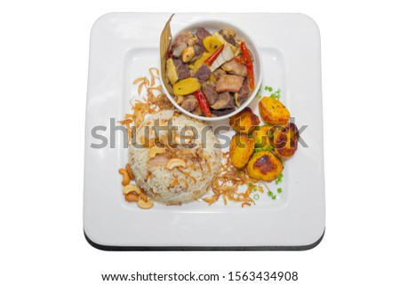 A plate of home chef Beef Kata Masala, plane flavourful nutty pulao and little poteto fried. Top view. on white background. #1563434908