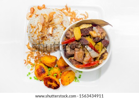 A plate of home chef Beef Kata Masala, plane flavourful nutty pulao and little poteto fried. Top view. on white background. #1563434911