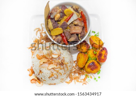 A plate of home chef Beef Kata Masala, plane flavourful nutty pulao and little poteto fried. Top view. on white background. #1563434917