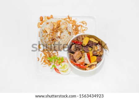 A plate of home chef Beef Kata Masala, plane flavourful nutty pulao and little poteto fried. Top view. on white background. #1563434923