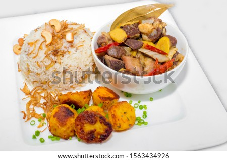 A plate of home chef Beef Kata Masala, plane flavourful nutty pulao and little poteto fried. Top view. on white background. #1563434926