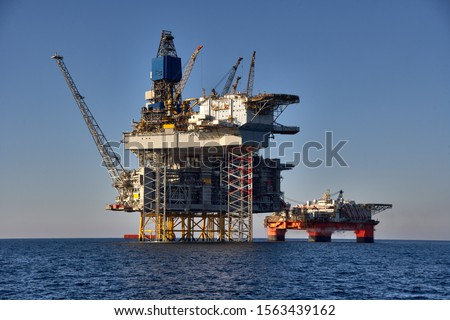 View of offshore oil and gas installation in a sunny day in sea.  Jack up, semi submersible rigs crude oil production in ocean. #1563439162