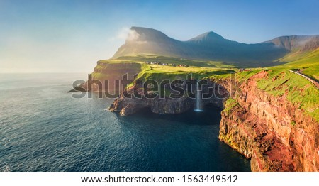 View from flying drone. Majestic morning scene of Mulafossur Waterfall. Stunning summer view of Vagar island, Faroe Islands,  Denmark, Europe. Beauty of nature concept background.