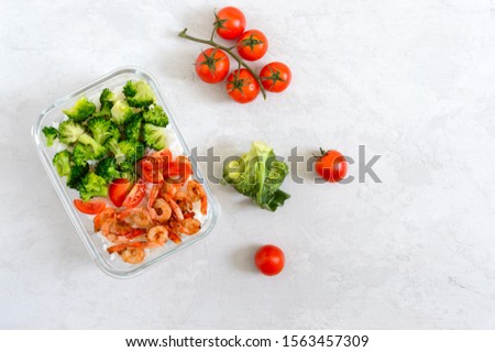 Glass lunch box with a useful lunch on a light background. Rice, broccoli, shrimp, fresh cherry tomatoes - healthy and tasty food. Proper nutrition. Sports diet. Top view #1563457309