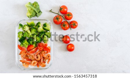 Glass lunch box with a useful lunch on a light background. Rice, broccoli, shrimp, fresh cherry tomatoes - healthy and tasty food. Proper nutrition. Sports diet. Top view #1563457318