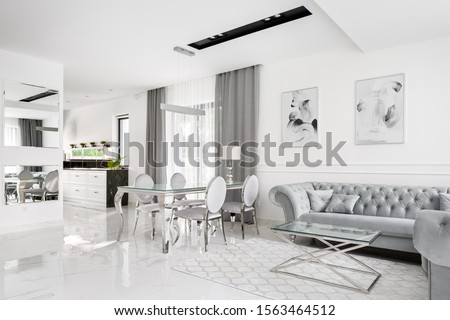 Glamour and romantic style home interior with kitchen open to living room with big dining table Royalty-Free Stock Photo #1563464512