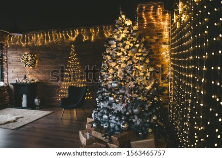 Christmas tree with many light bulbs and golden black decoration #1563465757