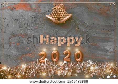 Candle numbers 2020, text happy 2020, bells and shiny sparkling Xmas garland with lights and tiny stars on dark rusty grunge textured background, panoramic picture. Merry Christmas and Happy New Year!