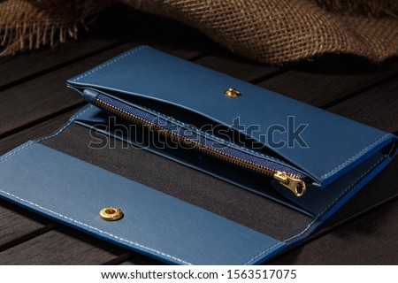 Blue Leather Long Wallet Lies on a Dark Wooden Table Royalty-Free Stock Photo #1563517075