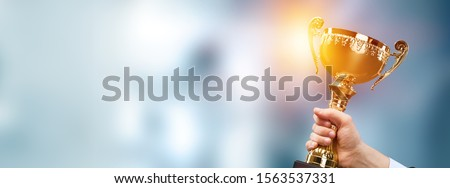 Champion golden trophy for winner background. Success and achievement concept. Sport and cup award theme. #1563537331