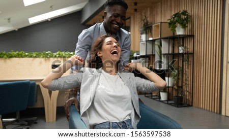 Happy african american young male employee giving chair ride to overjoyed caucasian female coworker at modern office. Laughing mixed race coworkers having fun, joking, enjoying pause at workplace. #1563597538