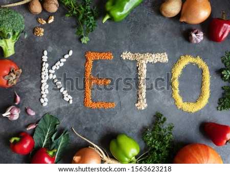 Frame of organic products: lentils, oatmeal, beans, millet on a dark gray background. Keto word made from ketogenic food. Keto, Ketogenic diet, low carb. Healthy food concept - top view. #1563623218
