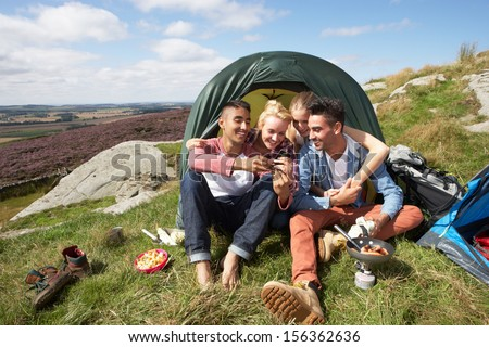 Group Of Young People Checking Mobile Phone On Camping Trip #156362636