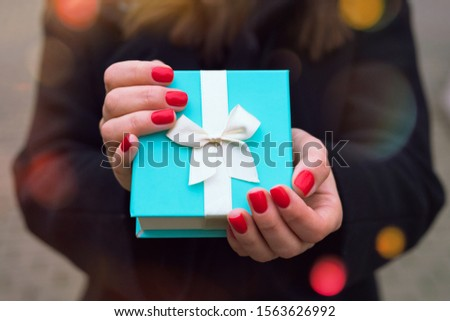 Beautiful blue gift box with a white ribbon in the hands of a girl with a red manicure in a black coat in a city park with bokeh. #1563626992