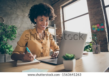Photo of cheerful joyful mixed-race woman in yellow shirt smiling toothily writing down notes holding training for students to be executives at laptop desktop table
