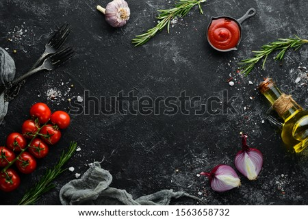 Black stone cooking background. Spices and vegetables. Top view. Free space for your text. #1563658732