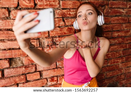 Photo of pleased woman in headphones taking selfie photo on cellphone while sending air kiss isolated over brick wall indoors