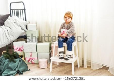 sad little girl holding gift in bedroom near bed #1563721351
