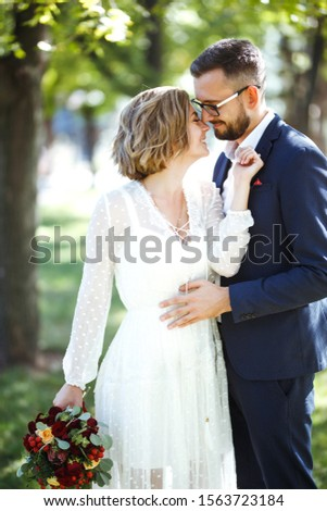 Young couple enjoying romantic moments while walking in the park. Stylish bride and groom posing and kissing in the park on their wedding day. Elegant bride in beautiful white dress, groom in a suit. #1563723184