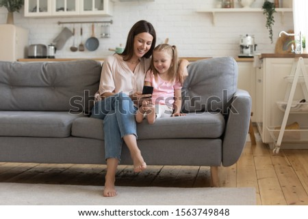 Full length front view happy 30s woman sitting on sofa with preschool daughter, looking at cellphone screen, watching funny cartoons, making selfie, holding call or recording video for social network. #1563749848