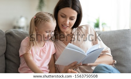 Head shot pleasant young mother sitting on couch with adorable kid girl, reading fairy tales together. Involved small daughter looking in book with interesting stories, enjoying relaxing time at home.