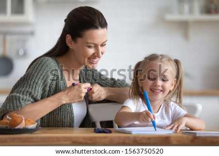 Head shot happy young mother sitting at table with adorable small preschool daughter, teaching drawing pictures or writing letters with colorful markers. Early children development education concept.