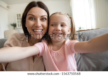 Web camera view funny little preschool girl posing with joking happy mother for photo at home. Overjoyed laughing mother posing for selfie with kidding small daughter in living room in apartment. #1563750568