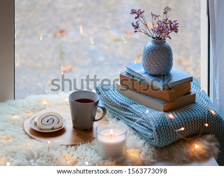 Cozy home. Winter holidays still life. Cup of tea with sweet dessert, candle, books, flowers in blue vase and garland lights at window. Relaxing at cold season at home. Copy space #1563773098