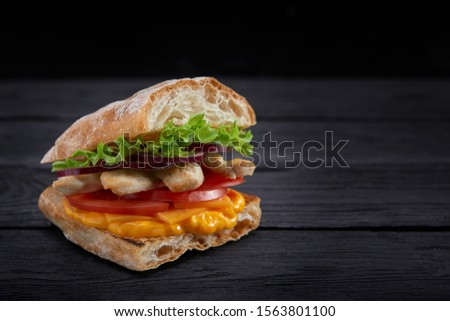 Appetizing sandwich on a wooden board. Baguette sandwich with filling from lettuce, slices tomato. Dark wooden background. View from above. Close-up. Macro photography. #1563801100
