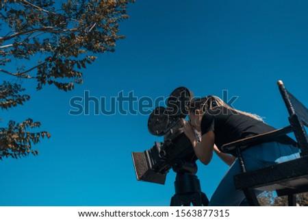 female cinema director looking at camera viewfinder #1563877315