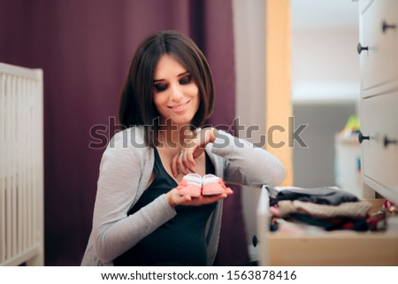 Cheerful Pregnant Woman Holding Small Infant Shoes. Mother to be expecting baby girl arranging nursery  #1563878416