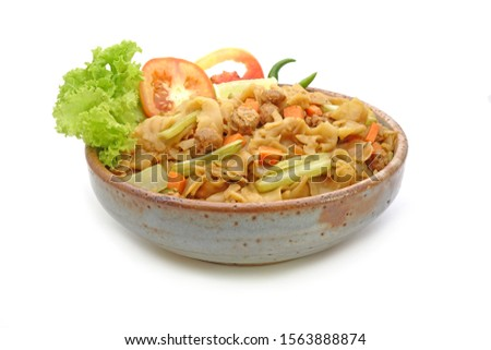Stir fried flat noodle with black soy sauce, tofu, carrots and green vegetables, isolated on white background. Vegetarian food for vegetarian festival. Thai style stir fry flat noodle. (Pad See Ew) #1563888874