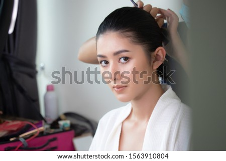 Professional makeup artist working with beautiful young asian woman model. Stylist makes hair hairstyles model. Preparing before her wedding or event. #1563910804