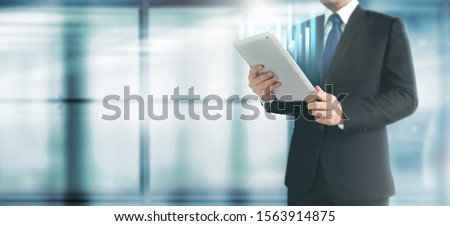 Businessman plan graph growth and increase of chart positive indicators in his business,tablet in hand #1563914875