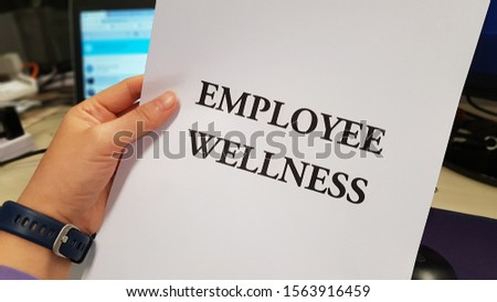 A hand holding a paper printed with the words Employee Wellness #1563916459