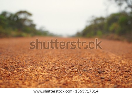 picture showing a road in the australian outback, red gravel dirt road