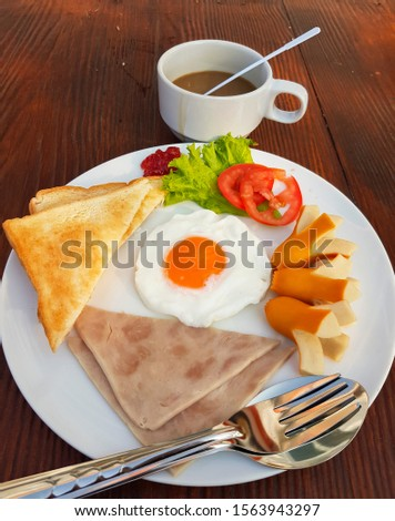 American breakfast includes fried egg, filling, ham, toast, lettuce and tomato, sliced on a white plate and coffee on a wooden table. #1563943297