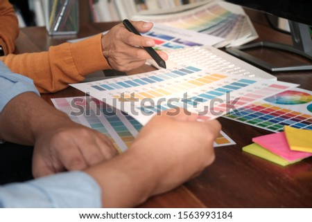 Graphic designer working on digital tablet. artist drawing on graphic tablet and Color swatch samples #1563993184