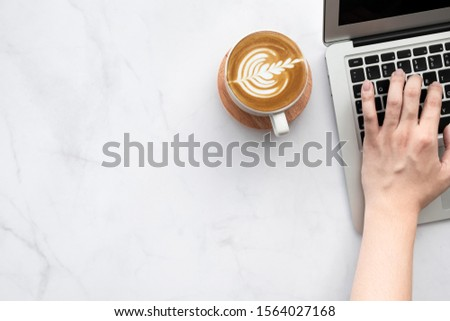 Man hand is typing on laptop computer keyboard over white marble office desk table with a cup of latte coffee. Top view with copy space, flat lay. #1564027168