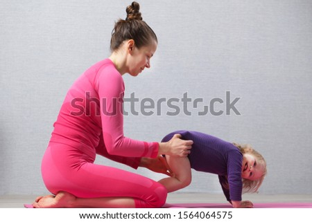 Hatha yoga home . fitness concept. mother in pink sportwear training with kid  #1564064575