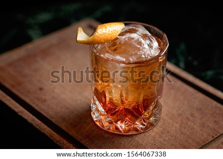 Old fashioned, classic cocktail served on the rocks  Royalty-Free Stock Photo #1564067338