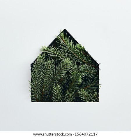 Christmas minimal concept - simple house silhouette made of christmas tree branch. Flat lat, top view. Square composition. Retro invitation for celebration design. Background clean. Abstract house.